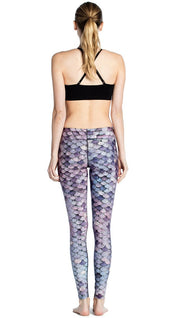 back view of model wearing purple mermaid scale themed printed full length leggings