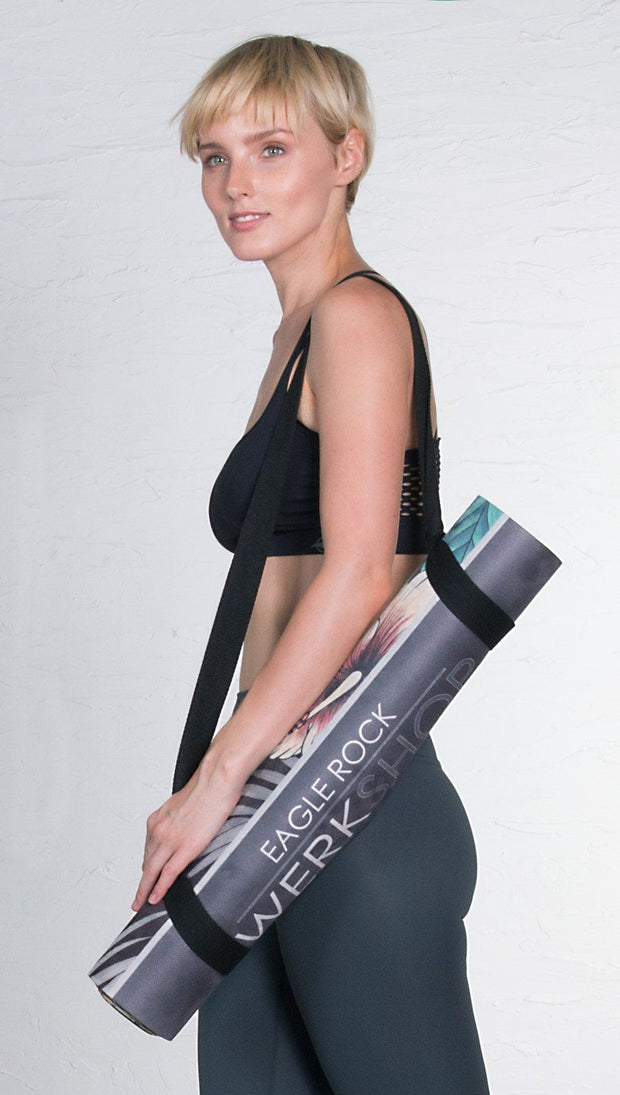 left side view of model carrying a rolled up printed yoga mat with tropical floral design