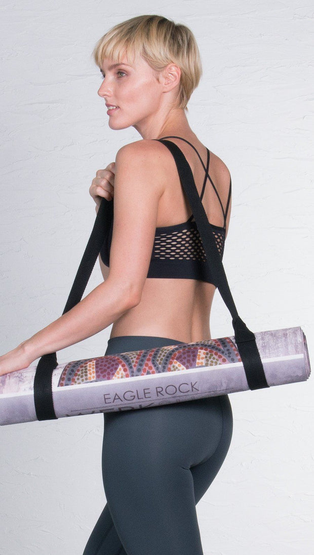 view of model carrying rolled up sugar skull yoga mat