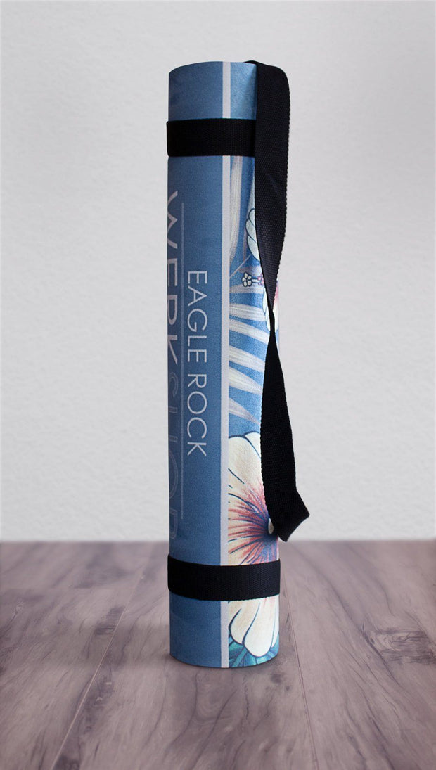 view of rolled up yoga mat with tropical floral design and blue background