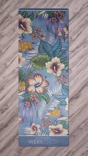 top view of yoga mat with tropical floral design and blue background