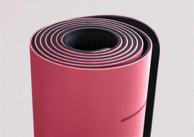 Closeup view of edge of rolled pink yoga mat