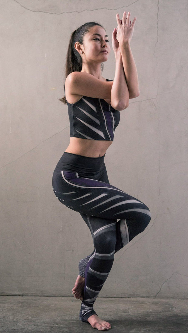 Model in standing yoga pose wearing black printed full-length leggings with purple and gray stripe design and matching sports top