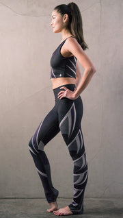 Left side view of model wearing black printed full-length leggings with purple and gray stripe design and matching sports top