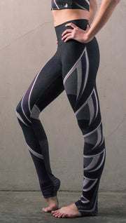 Left side view of model wearing black printed full-length leggings with purple and gray stripe design