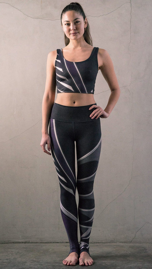 Front view of model wearing black printed full-length leggings with purple and gray stripe design and matching sports top
