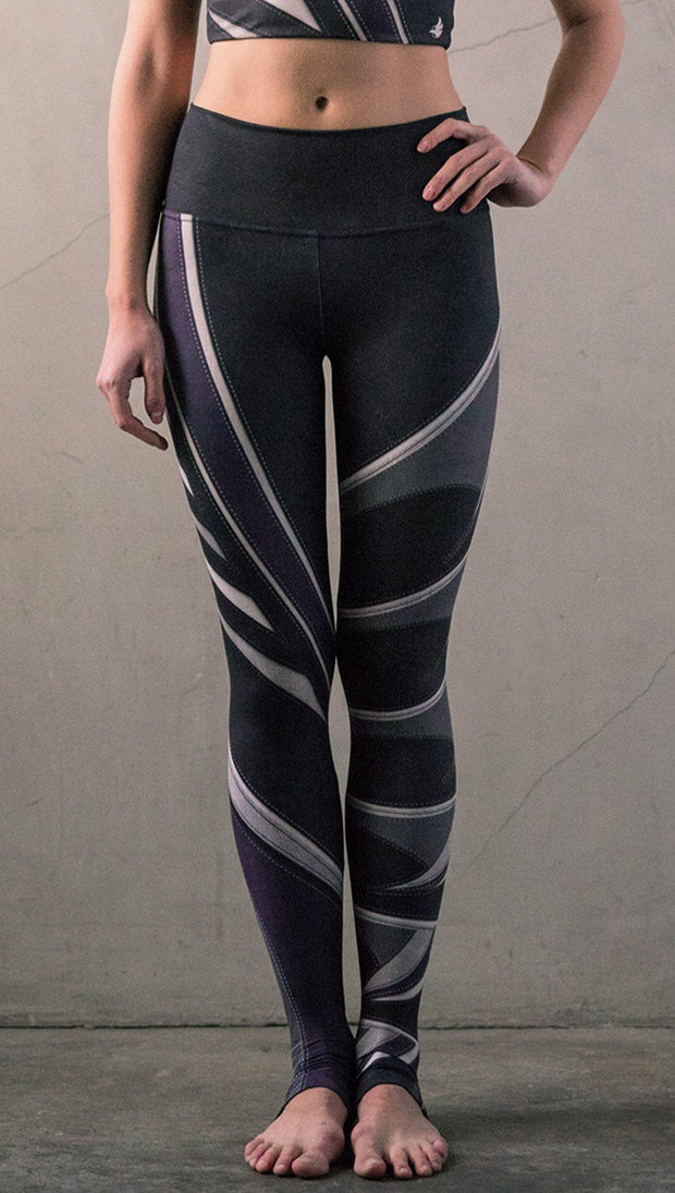 Front view of model wearing black printed full-length leggings with purple and gray stripe design