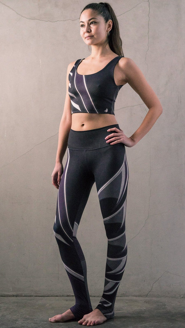 Slightly turned view of model wearing black printed full-length leggings with purple and gray stripe design and matching sports top
