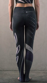 Rear view of model wearing black printed full-length leggings with purple and gray stripe design