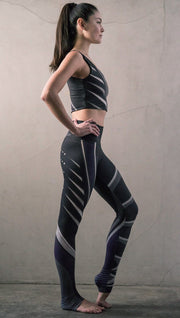 Right side view of model wearing black printed full-length leggings with purple and gray stripe design and matching sports top