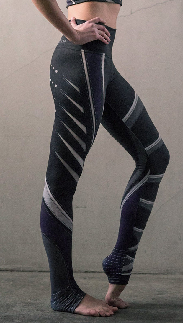 Right side view of model wearing black printed full-length leggings with purple and gray stripe design