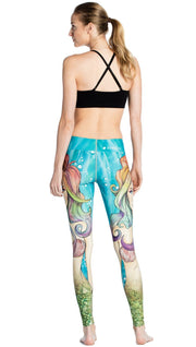 back view of model wearing colorful mermaid face themed printed full length leggings