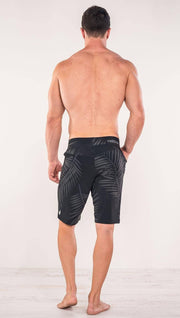 Back view of model wearing tropical palm fronds printed men's performance shorts
