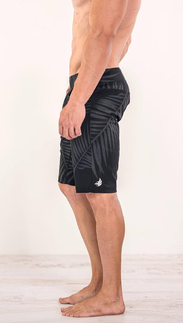 Close up right side view of model wearing tropical palm fronds printed men's performance shorts