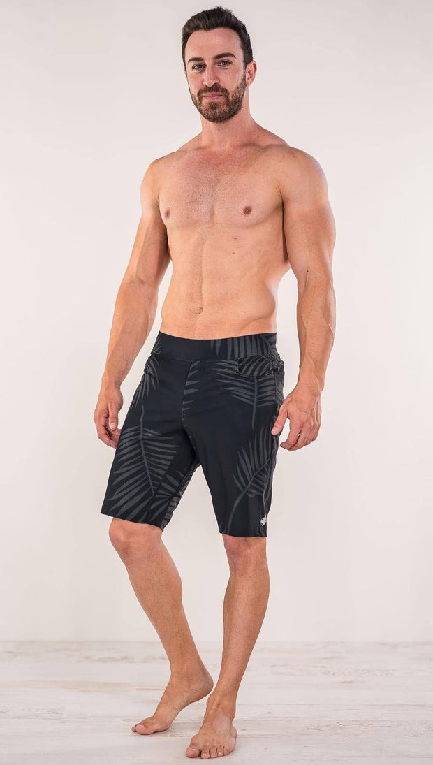 Front view of model wearing tropical palm fronds printed men's performance shorts