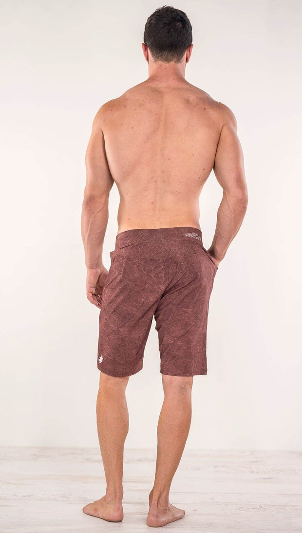 Back view of model wearing brick red printed men's performance shorts