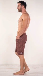 Left view of model wearing brick red printed men's performance shorts