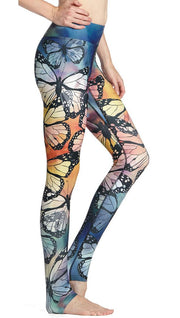 right side view of model wearing colorful butterfly themed printed full length triathlon leggings