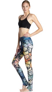 slightly turned front view of model wearing colorful butterfly themed printed full length triathlon leggings and sports top