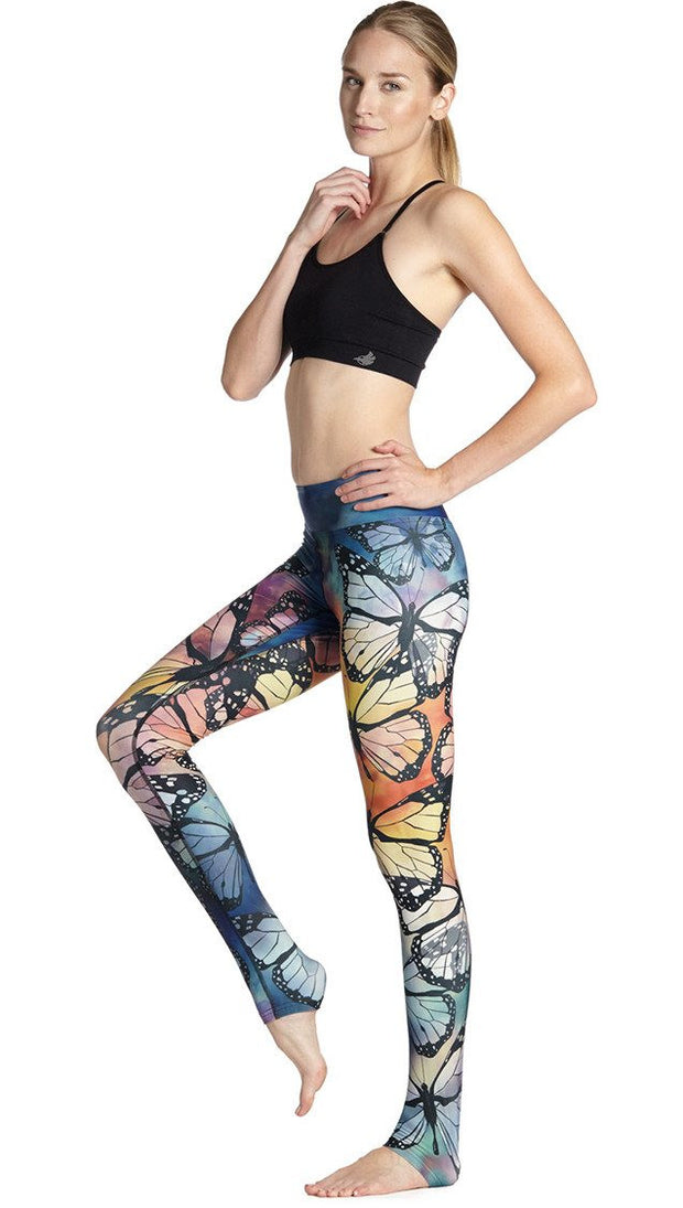 left side view of model wearing colorful butterfly themed printed full length triathlon leggings and sports top