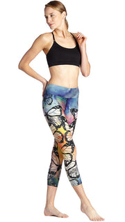 slightly turned front view of model wearing colorful butterfly themed printed capri triathlon leggings and sports top