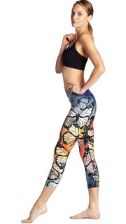 left side view of model wearing colorful butterfly themed printed capri triathlon leggings and sports top