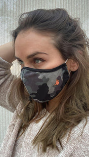Left side view of model wearing a green camouflage mask with the WERKSHOP logo in orange on the bottom corner