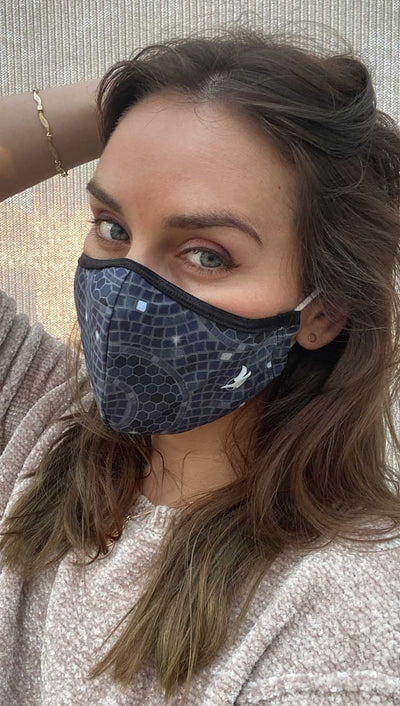 Left side view of model wearing a dark blue mosaic themed mask