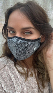 Slightly turned front view of model wearing a black mask with chainmaille