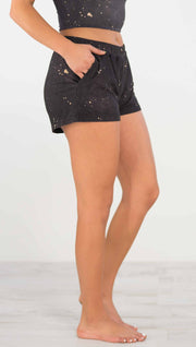 Right side view of model wearing a dark charcoal colored mid rise shorts with beige splatter spots throughout and a pocket in the front