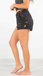 Left side view of model wearing a dark charcoal colored mid rise shorts with beige splatter spots throughout and a pocket in the front