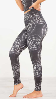 Left view of model wearing the charcoal athleisure leggings. It is in a charcoal color and has white tie dye circles throughout. Each circle has a smaller circle within each other