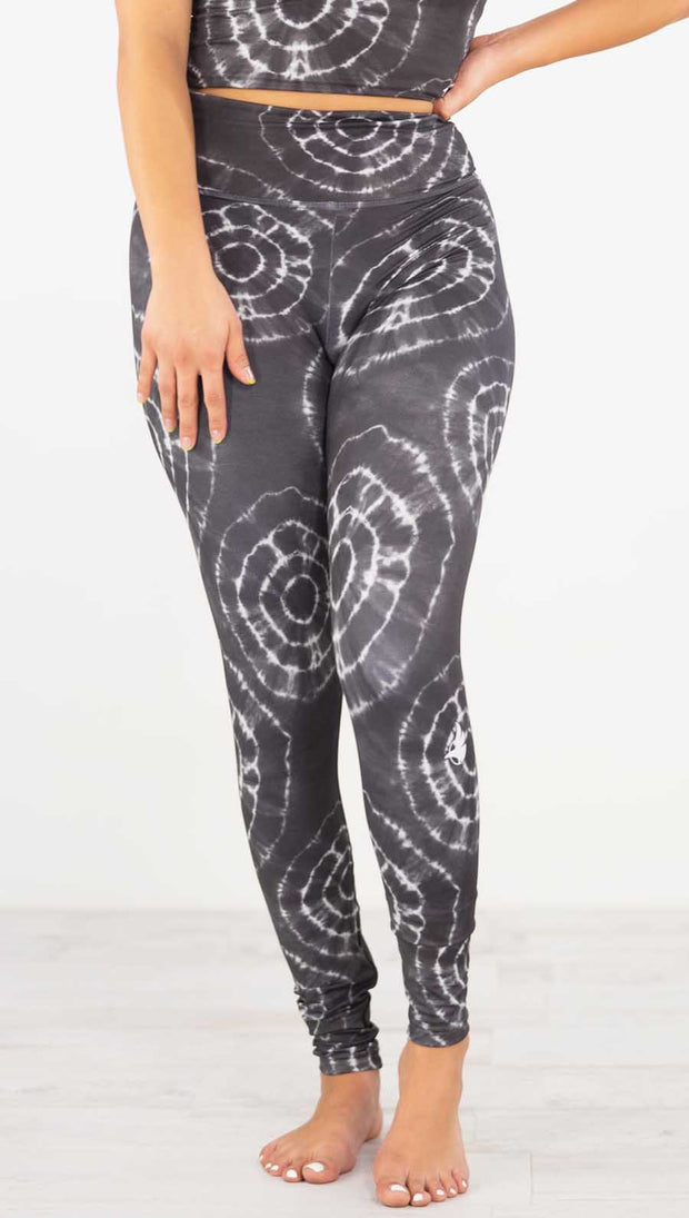 Front view of model wearing the charcoal athleisure leggings. It is in a charcoal color and has white tie dye circles throughout. Each circle has a smaller circle within each other
