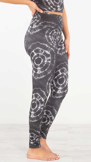 Right side view of model wearing the charcoal athleisure leggings. They are in a charcoal color and have white tie dye circles throughout. Each circle has a smaller circle within each other.