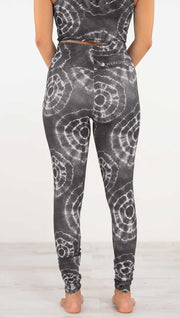 Back view of model wearing the charcoal athleisure leggings. They are in a charcoal color and have white tie dye circles throughout. Each circle has a smaller circle within each other