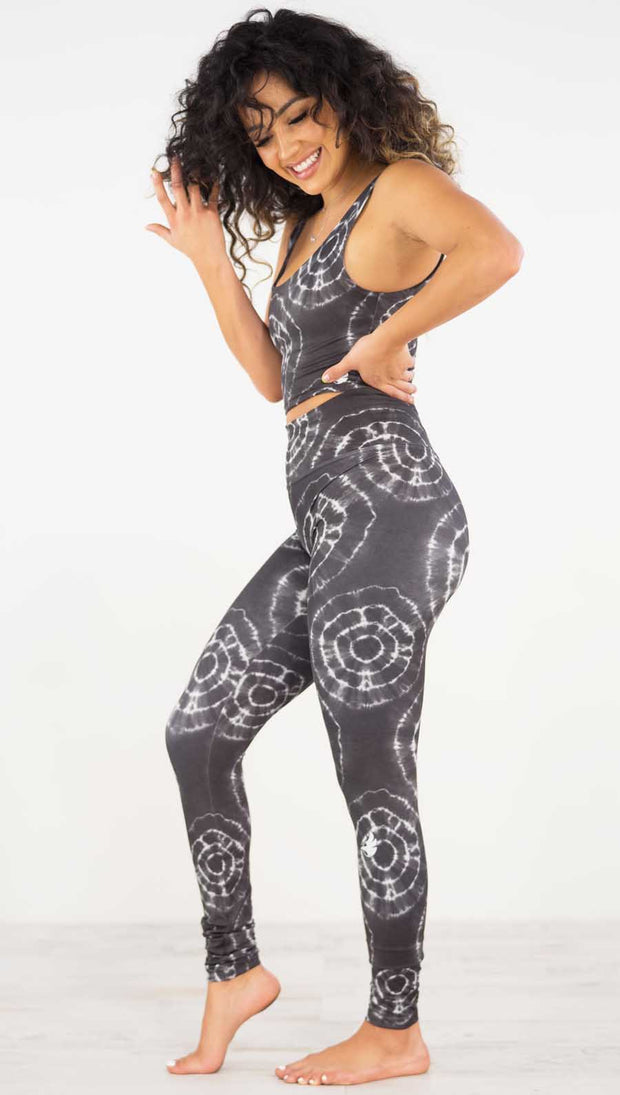 Left side view of model wearing the charcoal athleisure leggings. They are in a charcoal color and have white tie dye circles throughout. Each circle has a smaller circle within each other.
