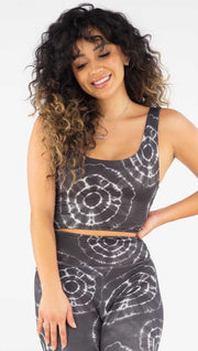 Front view of model wearing the reversible charcoal circles/ spiral crop top. This is the circles side. It has white tie dye circles throughout. Each circle has a smaller circle within each other.