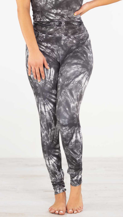 Front view of model wearing the charcoal spiral athleisure leggings. They are in a charcoal color with white tie dye spirals throughout the leggings.