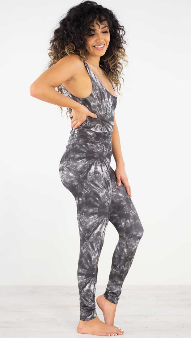 Right side view of model wearing the charcoal spiral athleisure leggings. They are in a charcoal color and have white tie dye spirals throughout the leggings.