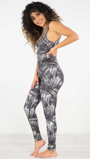 Left side view of model wearing the charcoal spiral athleisure leggings. They are in a charcoal color and have white tie dye spirals throughout the leggings.