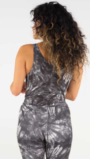 Back view of model wearing the reversible charcoal circles/ spiral crop top. This is the spiral side. It is in a charcoal color with white tie dye spirals throughout the top.