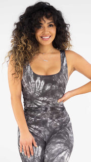 Front view of model wearing the reversible charcoal circles/ spiral crop top. This side is spiral side. It is a charcoal color and has white tie dye spirals throughout the top.