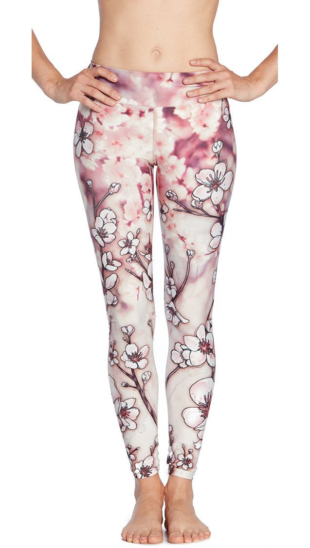 close up side view of model wearing cherry blossom themed printed full length leggings
