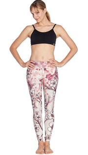front view of model wearing cherry blossom themed printed full length leggings and sports top