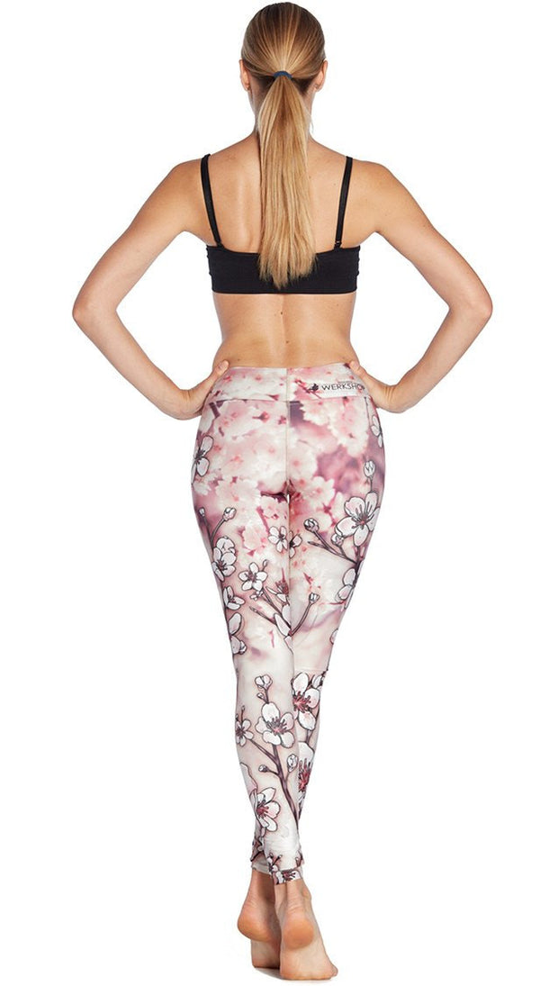 back view of model wearing cherry blossom themed printed full length leggings and sports top