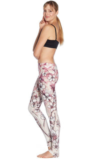 left side view of model wearing cherry blossom themed printed full length leggings and sports top