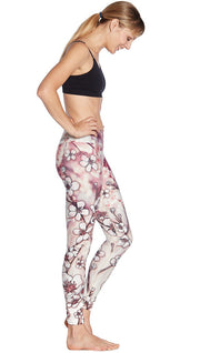 right side view of model wearing cherry blossom themed printed full length leggings and sports top