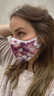 Left side view of model wearing a pink cherry blossom mask