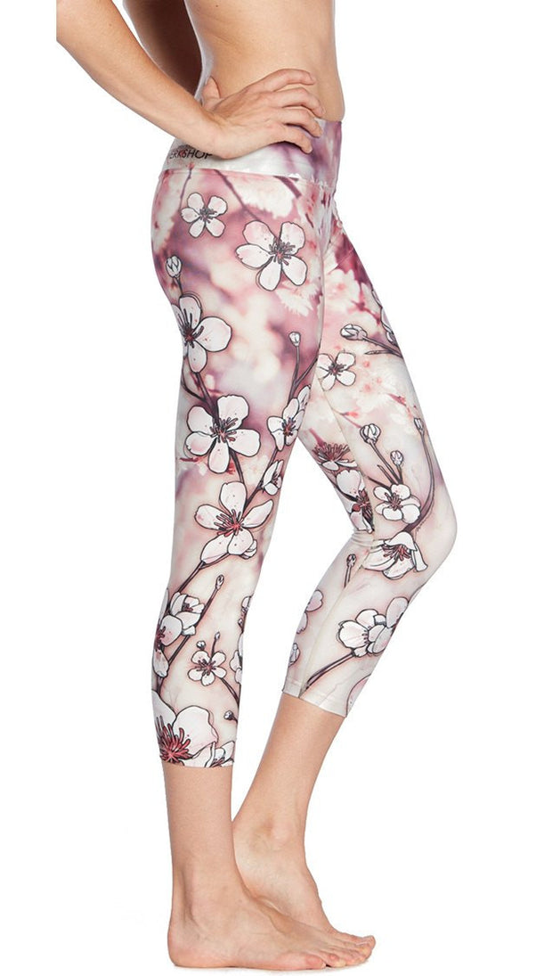 closeup right side view of model wearing cherry blossom themed printed capri leggings