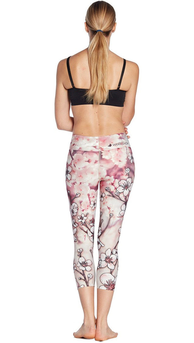 back view of model wearing cherry blossom themed printed capri leggings and sports top